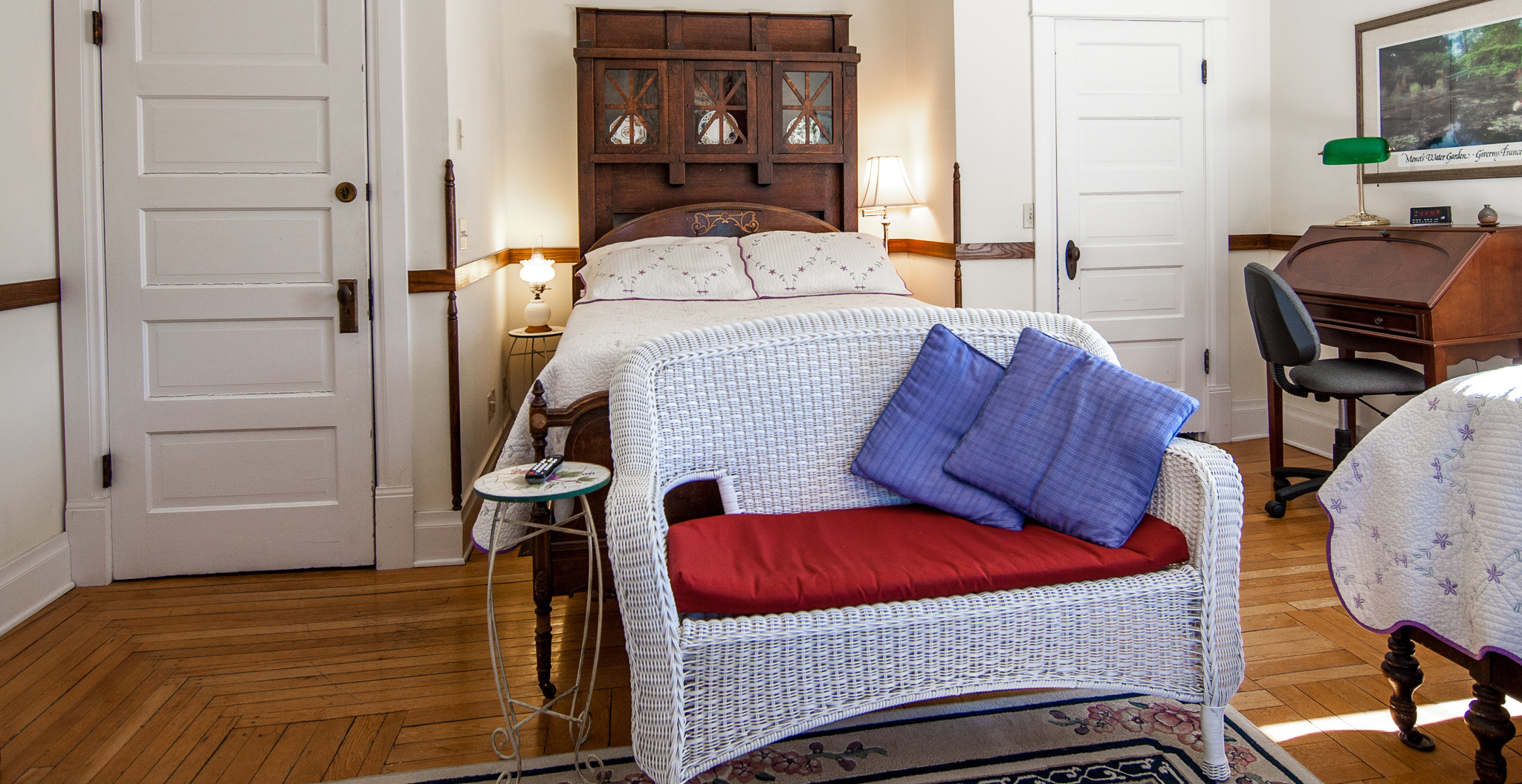 A wicker bench with blue pillows in the Bluestone Room in our B&B near JMU.