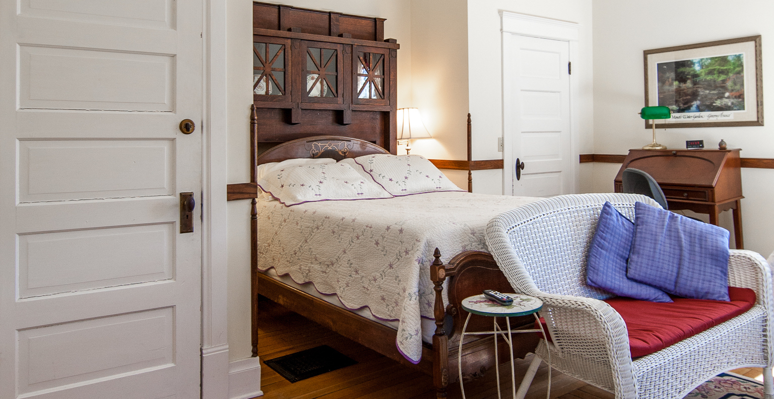 A full bed and white wicker bench in the Bluestone Room. Making it ideal lodging near Shenandoah National Park.